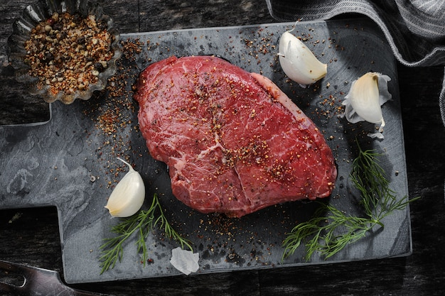 Carne cruda con spezie su superficie scura. pronto per la cottura.