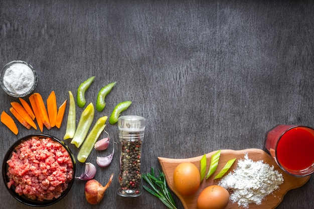 Carne cruda con verdure e spezie su fondo in legno