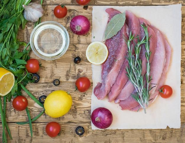Carne cruda di maiale affettata con spezie e verdure