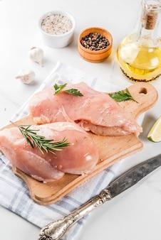 Carne cruda, filetto di petto di pollo, con olio d'oliva, erbe e spezie su fondo di marmo bianco, copia spazio