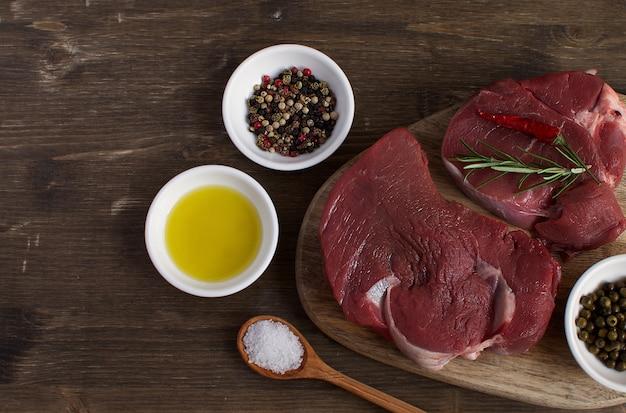 Carne cruda fresca bistecca di manzo olio d'oliva spezie sale caldo cucchiaio di legno peperoncino rosmarino concetto di cottura concetto di cottura vista dall'alto copia spazio piatto