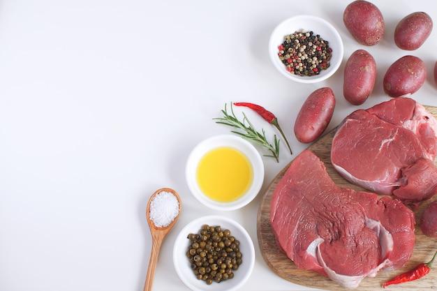 Carne cruda fresca bistecca di manzo olio d'oliva spezie sale sfondo bianco vista dall'alto copia spazio piatto lay