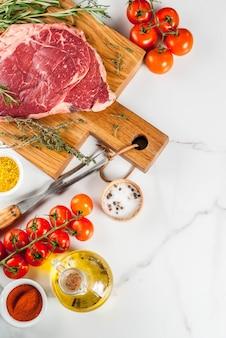 Carne cruda fresca, bistecca di marmo di manzo d'agnello su un tagliere, con ingredienti per cucinare. sul tavolo di marmo bianco, copyspace vista dall'alto