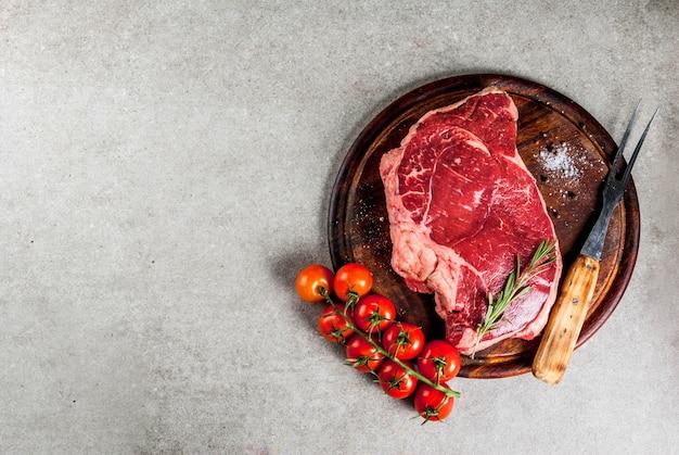 Carne cruda fresca, bistecca di marmo di manzo d'agnello su un tagliere, con ingredienti per cucinare. sul tavolo di pietra grigia, copyspace vista dall'alto