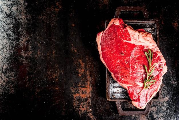 Carne cruda fresca, bistecca di marmo di manzo di agnello su una griglia padella, con ingredienti per cucinare. sul tavolo di metallo arrugginito scuro, copyspace vista dall'alto