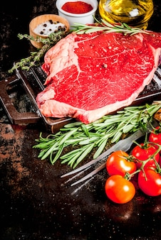 Carne cruda fresca, bistecca di marmo di manzo di agnello su una griglia padella, con ingredienti per cucinare. sul tavolo di metallo arrugginito scuro, copyspace
