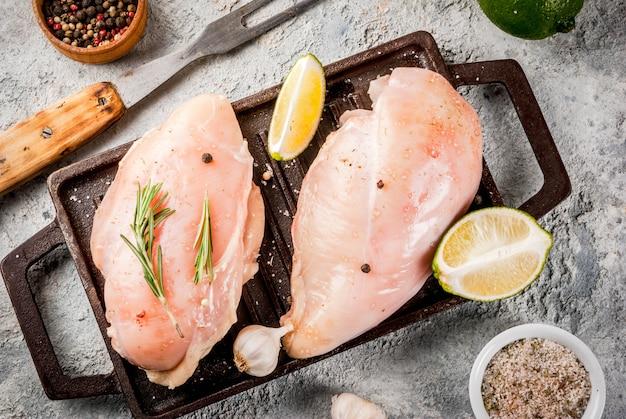 Carne cruda pronta per griglia o barbecue filetto di petto di pollo con erbe e spezie olio d'oliva su sfondo grigio pietra