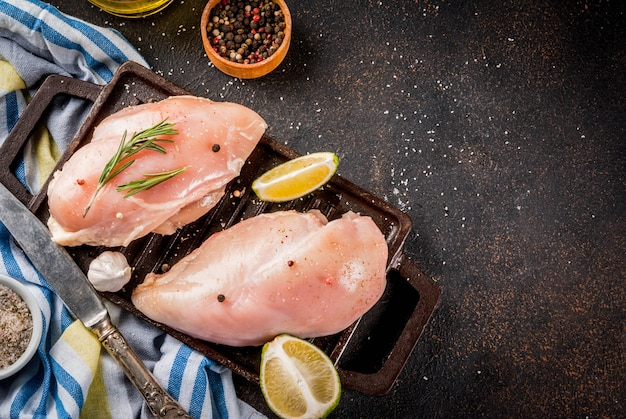 Carne cruda, pronta per griglia o filetto di petto di pollo al barbecue, con olio d'oliva, erbe e spezie