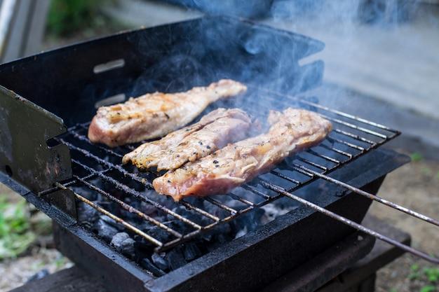 Carne di bistecca di maiale all'aperto sulla griglia del barbecue, fatta in casa, maiale barbecue fatto in casa e griglia di pollo