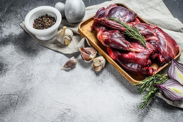 Carne di lepre lepre selvaggia fresca cruda su una tavola di legno con le verdure e le spezie. vista dall'alto. copia spazio