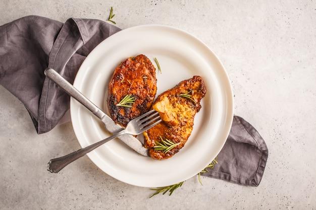 Carne di maiale al forno della bistecca con i rosmarini su un piatto bianco, vista superiore.