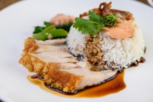 Carne di maiale croccante su un piatto bianco condita con salsa.