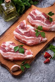 Carne di maiale cruda e ingredienti per cucinare. messa a fuoco selettiva