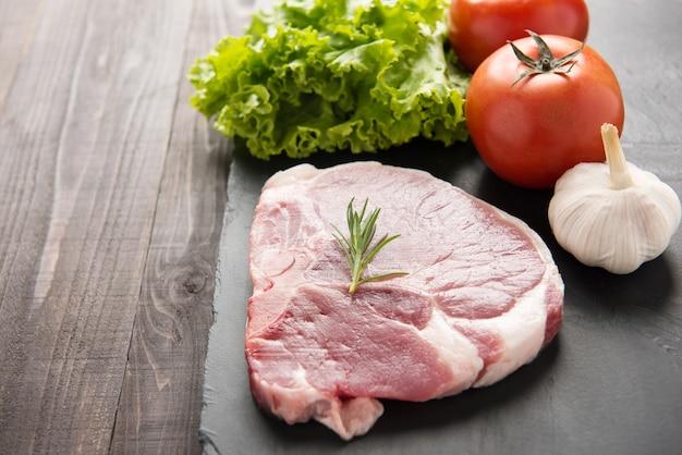Carne di maiale cruda sulla lavagna e verdure su fondo di legno
