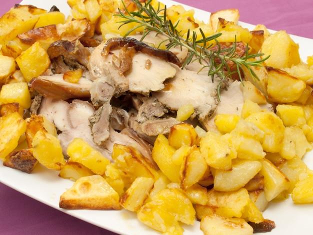 Carne di maiale e patate arrostite con olio d'oliva e rosmarino