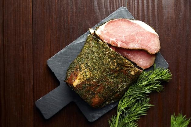 Carne di maiale essiccata, polendwitz, filetto a scatti, aneto verde fresco, tagliere di ardesia su fondo di legno, vista dall'alto. carne di maiale stagionata. la polenitsa è un filetto stagionato. piatto di cucina bielorussa