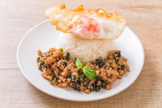 Carne di maiale saltata in padella con basilico su riso e uovo fritto