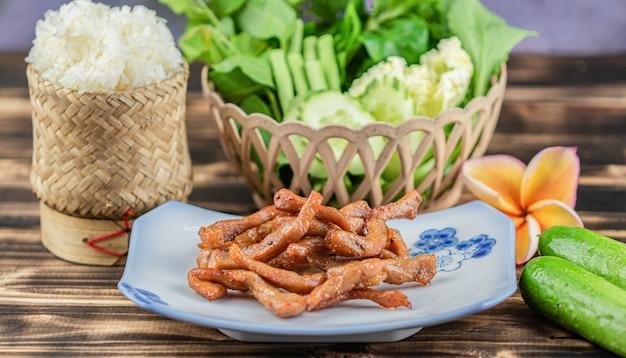 Carne di maiale seccata al sole fritta nel grasso bollente e riso appiccicoso sul fondo di legno della tavola.