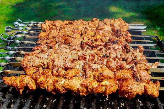 Carne di maiale su spiedini cotti sulla griglia del barbecue.