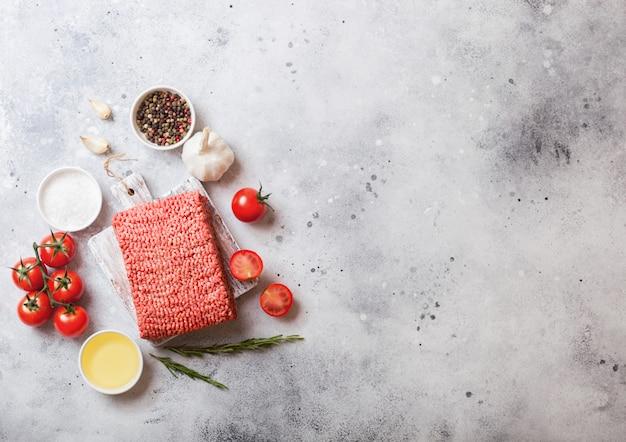 Carne di manzo fatta in casa tritata cruda con spezie ed erbe aromatiche. vista dall'alto. sulla parte superiore del tagliere e tavolo da cucina in marmo. con pepe sale e aglio.