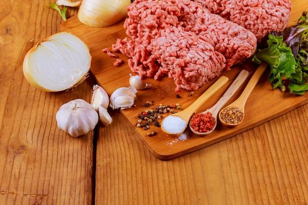 Carne di manzo macinata con foglie di basilico pronte per la cottura