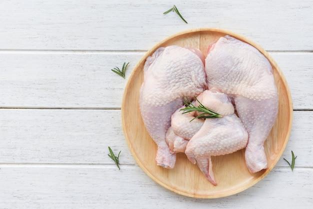 Carne di pollo cruda con rosmarino / coscia di pollo cruda fresca ed ala sul fondo di legno del piatto