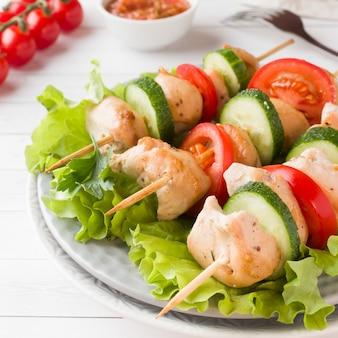Carne di pollo kebab tradizionale con pomodori, cetrioli e erbe fresche su un piatto.