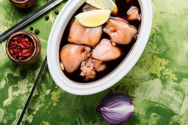 Carne di pollo marinata cruda