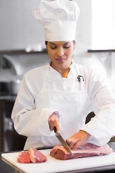 Carne di taglio femminile del cuoco unico in cucina