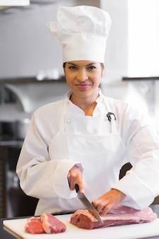 Carne di taglio sorridente del cuoco unico femminile in cucina