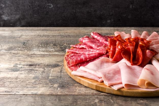 Carne fredda sul tagliere sulla tavola di legno contenente prosciutto, salame, mortadella di salsiccia e tacchino, spazio della copia