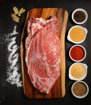 Carne fresca con ingredienti per cucinare sul tavolo scuro