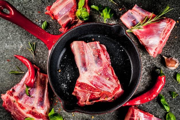 Carne fresca cruda, agnello crudo o costolette di manzo con peperoncino, aglio e spezie con padella padella su sfondo di pietra scura