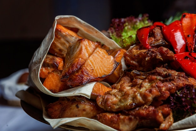 Carne grigliata mista, verdure fritte e filetto di salmone grigliato decorato in piatto caldo