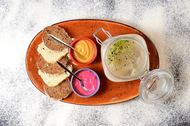 Carne in gelatina in un barattolo di vetro con rafano rosso, senape e crostini