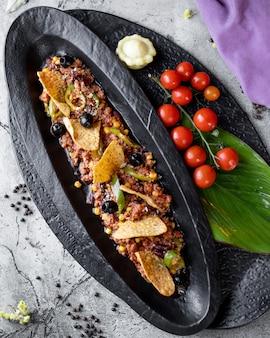 Carne macinata con mais, olive e pepe servita con tortilla chips