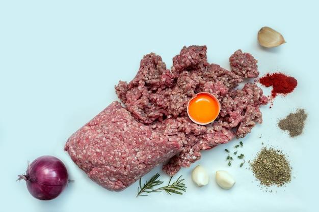Carne macinata cruda con pepe, uova, erbe e spezie per cucinare cotolette, hamburger, polpette di carne. concetto: cucina, ricette, piatti deliziosi. copia spazio