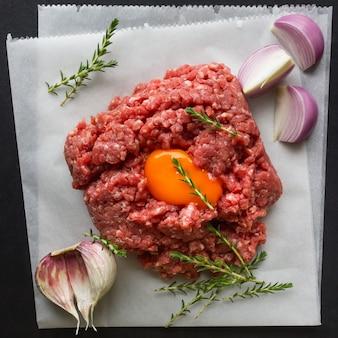 Carne macinata cruda con pepe, uova, erbe e spezie per cucinare cotolette, hamburger, polpette di carne.