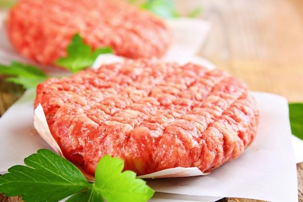 Carne macinata cruda per hamburger fatti in casa grigliati con spazi ed erbe.