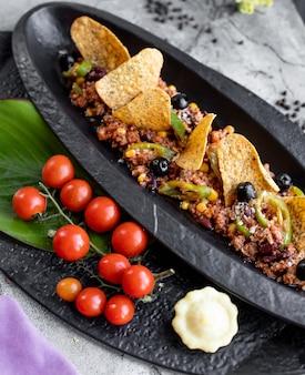 Carne macinata servita con olive al pepe di mais e tortilla chips