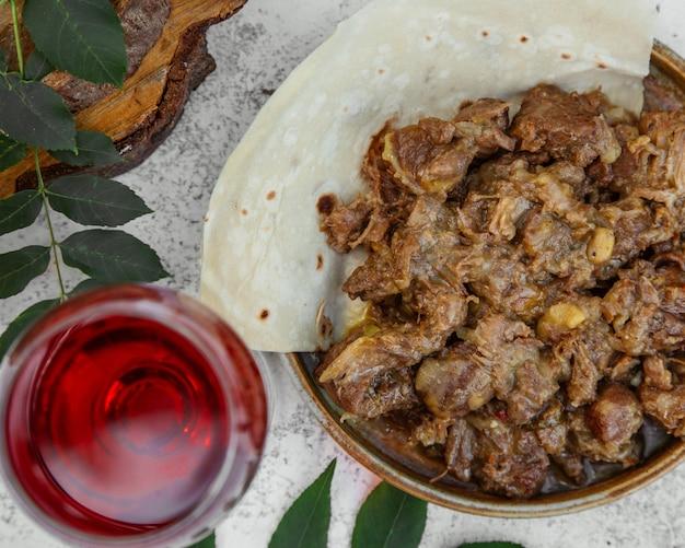Carne preparata in salsa e bicchiere di succo