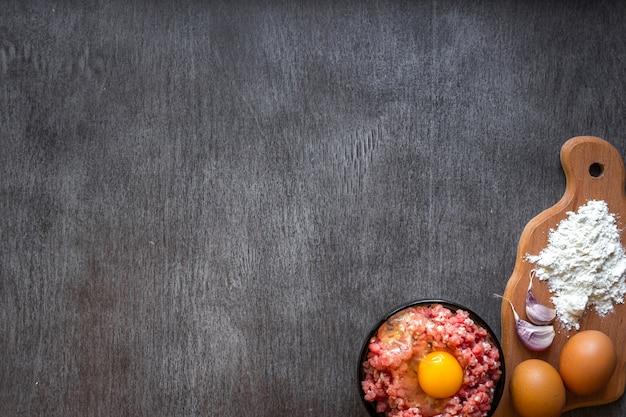 Carne tritata cruda con tuorlo d'uovo e tagliere di legno su fondo di legno