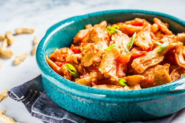 Carne vegana di soia in salsa di pomodoro in un piatto blu su uno sfondo di cemento grigio