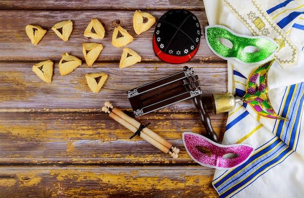 Carnevale ebraico purim celebrazione su biscotti hamantaschen, fabbricatore di rumori e maschera con pergamena