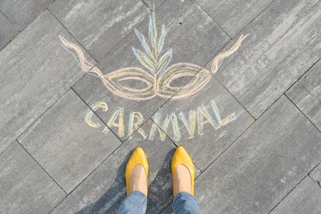 Carnevale scritto sul marciapiede grigio con le gambe delle donne in scarpe gialle
