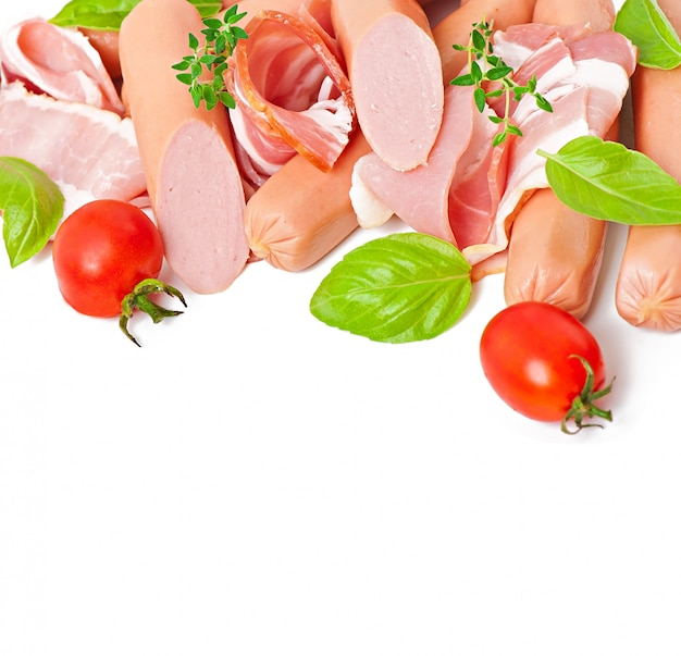 Carni delicate (salsiccia e prosciutto) decorate con basilico e pomodori isolati