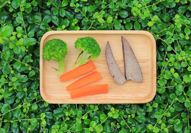 Carota e fegato dei broccoli nel posto di legno del vassoio sul fondo della foglia. alimenti biologici per l'infanzia.