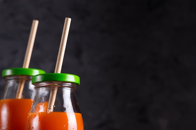 Carota e succo d'arancia in bottiglie di vetro con cannucce eco in chiave di basso vicino