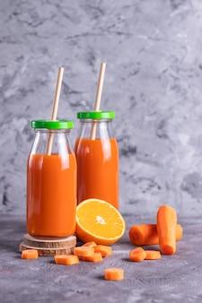 Carota e succo d'arancia in bottiglie di vetro con cannucce eco su sfondo grigio