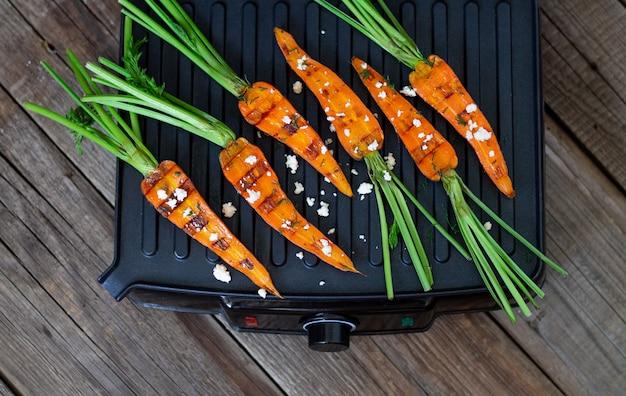 Carote al forno o arrostite sulla griglia sulla vista di legno del piano d'appoggio